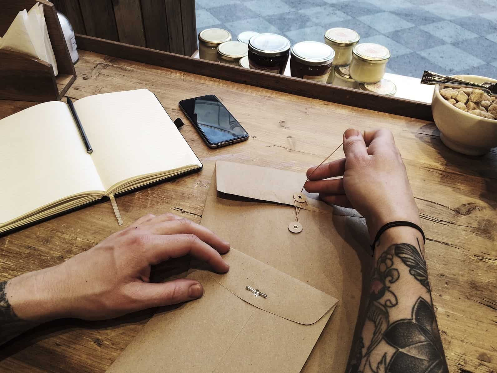 Man in cafe works with notebook, tattoo hands