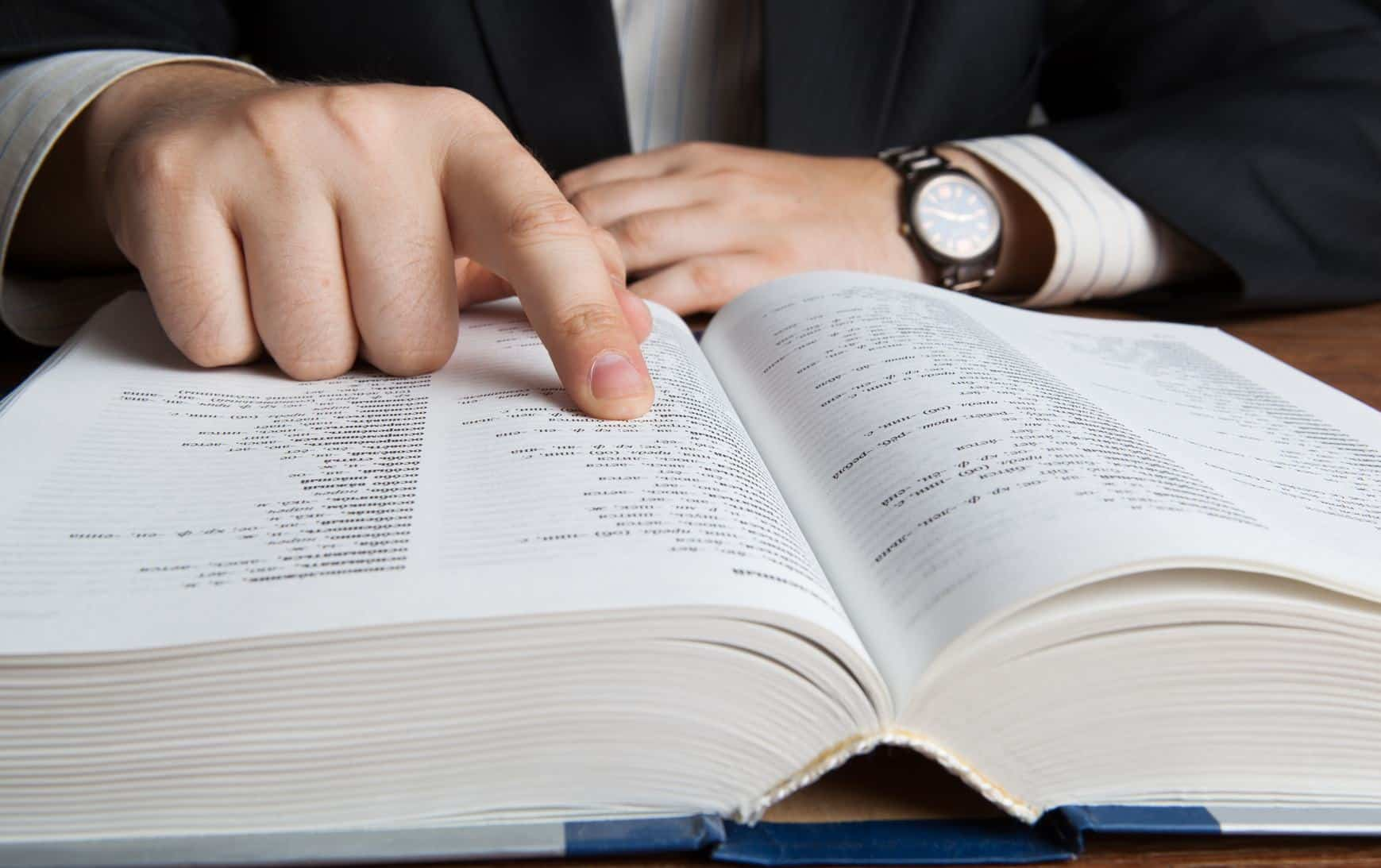 man looking in the large dictionary